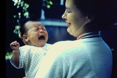 A photo of my mom hold a crying baby me in her arms.